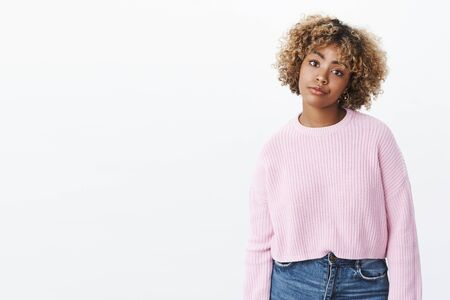 African-american girl looking with dismay and annoyance smirking from dislike and regret stooping with indifferent careless expression tilting head Stock Photo