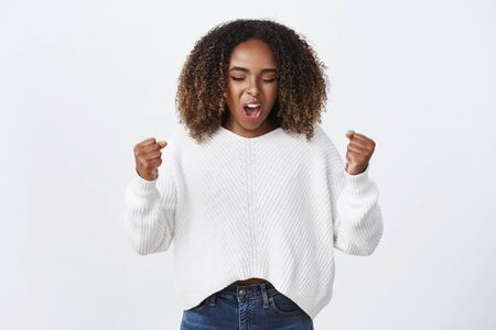 Portrait of cute emotive and excited charismatic dark-skinned female yelling in support and celebration clenching fists, encouraging and boosting confidence in herself 写真素材