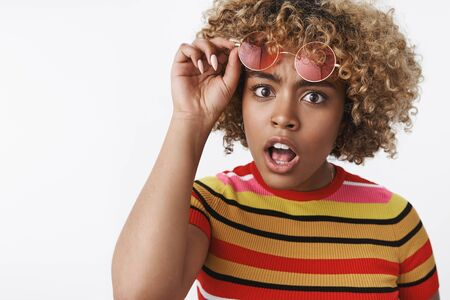 Impressed and astonished african american stylish woman with blond haircut raising eyebrows confused drop jaw and taking off glasses looking at camera