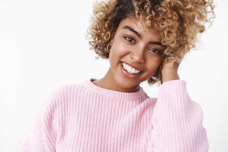 Toma interior de atractiva mujer afroamericana con peinado rizado tocando la mejilla con suavidad y ternura inclinando la cabeza y sonriendo abiertamente posando despreocupada con actitud feliz sobre fondo blanco.