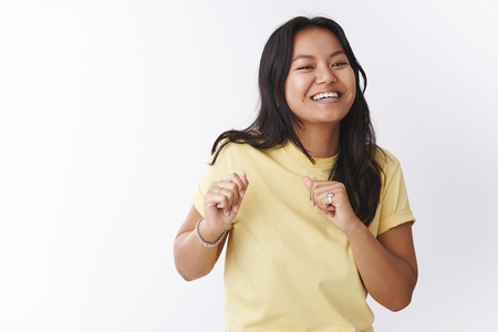 Studio shot of funny and enthusiastic upbeat joyful female in yellow t-shirt making dance moves shaking body and hands attending awesome party with cool music over white background