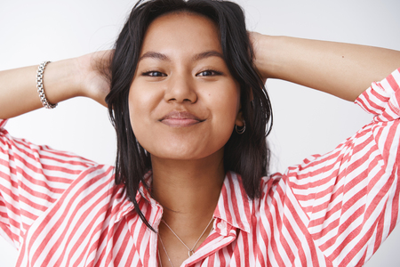 Close-up shot of woman love herself with flaws accepting own body feeling free and relaxed, happy smiling at camera raising head self-assured and holding hands behind in lazy pose over white wall