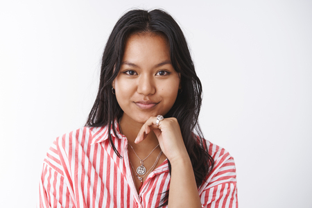 Confident and daring good-looking cheeky asian female in striped blouse touching chin and looking determined at camera having lots interesting and productive thoughts how establish business