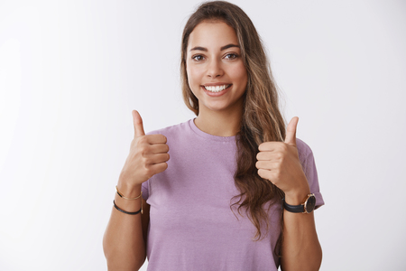 Waist-up shot energized outgoing charming young modern woman showing thumbs up smiling pleased approving, liking cool product, recommending, cheering rooting for boyfriend, standing white background