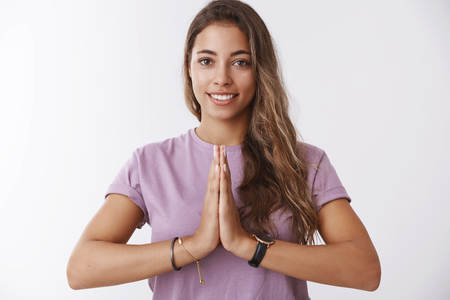 Attractive friendly smiling happy female practicing yoga meditating grinning relived calm, feeling peaceful, pressing palms together namaste praying gesture, asian welcoming, standing white wall