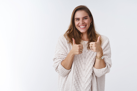 Nice work keep up. Portrait supportive charming outgoing attractive young modern woman showing thumbs up smiling broadly happy giving approval gesture agree, liking awesome product, accepting