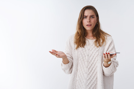 What heck. Portrait frustrated pissed questioned clueless woman arguing holding smartphone shrugging hands spread dismay frowning perplexed open mouth talking intense, white background Reklamní fotografie