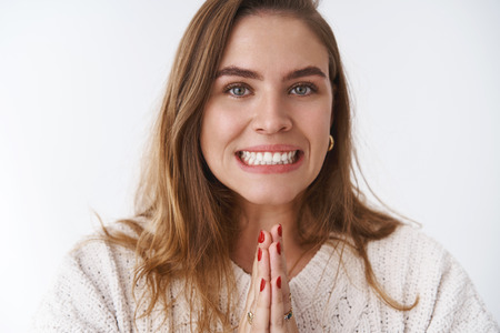 Clse-up charming charismatic cute upbeat adult woman asking friend rescue cover-up work, holding hands pray smiling needy, begging help standing supplicating white background, praying hopefully