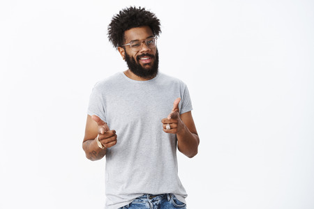 Guy winking flirty, pointing with finger pistols at camera after saying catchy phrase as standing in mirror encouraging himself for good mood, standing with curly hair and pierced nose over gray wall