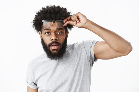 Impressed and surprised handsome african american guy taking off glasses as being charmed, holding eyewear on forehead open mouth from amazement gazing at camera over gray wall