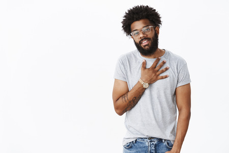 Portrait of thankful cool and stylish african american guy holding palm on heart and smiling grateful giving thanks friends for help over gray background