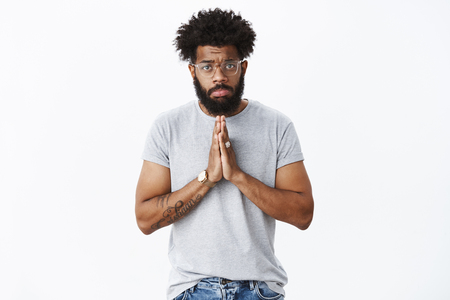 Sad and gloomy african american guy with pierced nose, tattoos wearing glasses pouting upset holding hands in pray over chest, frowning begging for mercy and help, asking favour or sorry