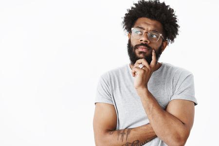 Afroamerikaner mit Brille, der einen Plan im Kopf macht, der sich eine Einkaufsliste ausdenkt und die Hand am Bart hält, die nachdenklich nach links schaut, die Stirn runzelt, als er überlegt, welche Wahl richtig ist, um eine neue Idee über grauer Wand zu schaffen?