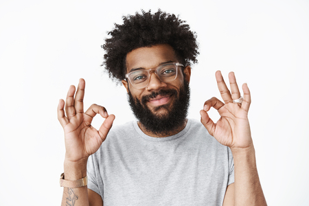 Close-up shot of kind and friendly adult african american bearded guy with pierced nose and afro hairstyle smiling delighted and sincere showing okay gesture, feeling fine confirming work done