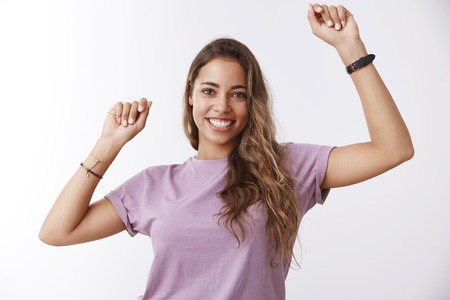 Girl performing victory dance. Enthusiastic charismatic attractive young woman raising hands high moving music rhythm celebrating successful achievement goal, smiling happily, having fun