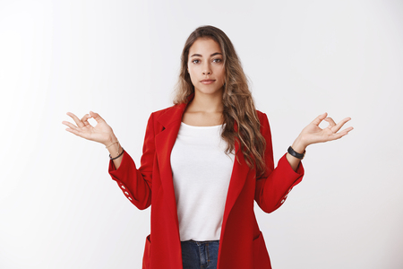 Confident calm modern successful businesswoman keeping feelings under control, showing lotus pose mudra gesture standing nirvana peacefully, stress-free, meditating standing office white background