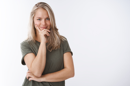 Portrait of self-assured creative female sportswoman making plan smirking delighted and confident leaning face on fingers looking daring at camera over white background