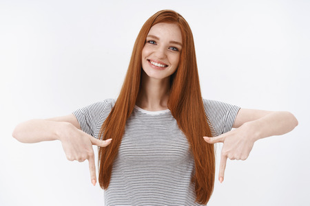 Waist-up tender good-looking redhead young female student tilting head smiling delighted white teeth pointing satisfied index fingers down joyfully discussing interesting product downwards