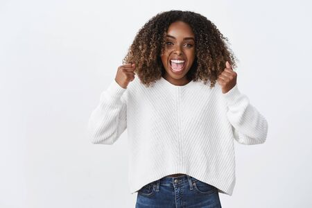 Excited happy good-looking female african-american woman curly afro hairstyle cheering happy yelling yes accomplished goal, dream come true, success achieved, celebrating, triumphing happily