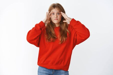 Girl shocked cannot understant what happening standing confused and perplexed with mind blowing out from information holding hands on temples lifting eyebrows questioned wearing red sweater
