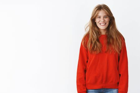 Portrait of charming energized and optimistic sportswoman with natural beautiful hair in stylish red oversized warm sweater smiling joyfully expressing friendly and positive mood over gray background Stok Fotoğraf