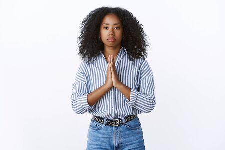 Serious-looking african american troubled girl need help praying holding hands pray supplicating, palms pressed together please do favour, begging standing gloomy intense worried white background