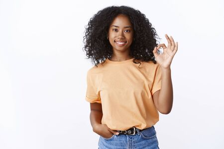 Charming friendly-looking stylish african-american girl say no problem showing ok excellent gesture smiling satisfied with good result 写真素材