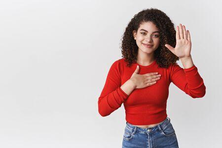 Prometti di dire la verità. Affascinante felice rilassato sincero giovane ragazza dai capelli ricci supplica giuramento giurare tenere la mano cuore sollevare palmo facendo dichiarazione sorridente felicemente, in piedi sfondo bianco Archivio Fotografico