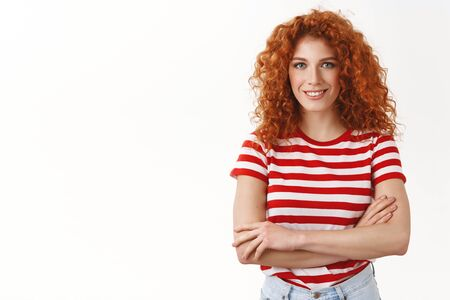 Self-assured attractive young redhead curly enthusiastic girl starting up new project feel determined enouraged success cross arms chest smiling assertive powerful women concept, white background Stockfoto
