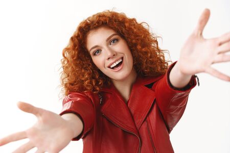 Come into my arms. Attractive stylish flirty ginger girl curly hairstyle reach hands camera wanna hug cuddle inviting embrace friend smiling broadly wanna hold boyfriend tight, white background