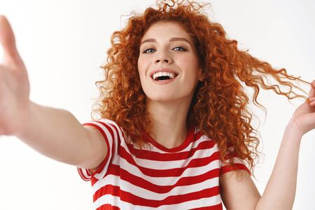 Stylish good-looking cheeky redhead curly blue-eyed woman smiling white teeth playing hairstyle flirty laughing record emotions video hold camera hand towards taking selfie smartphone, blogging