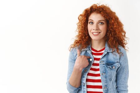 Who me. Gorgeous redhead femenine woman surprised being chosen pointing herself index finger smiling broadly standing delighted wondered receive compliment interesting suggestion, white background