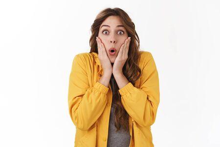 Fille émotive bavarde choquée abasourdie se demandant rumeur surprenante entendre des nouvelles incroyables regarder caméra lèvres pliantes wow toucher joues étonné impressionné debout fond blanc