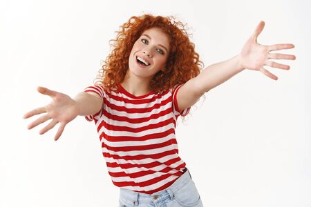Come on give me. Energized lively smiling optimistic redhead curly woman tilt head joyfully stretch hands forward hug cuddles wanna hold tight friend inviting embraces standing white background