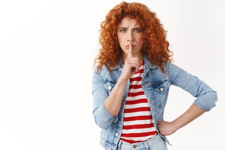 Upset redhead european girl curly hairstyle shushing show shhh sign index finger pressed lips frowning complaining loud noise asking keep quiet begging not tell secret standing white background