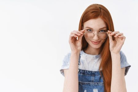 Cunning good-looking redhead sassy girlfriend put on glasses look from under forehead devious pleased have something curious in mind, smiling delighted stand white background assertive