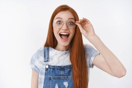 Lively redhead impressed happy girl wear denim overalls smiling amazed cheerful touch glasses look camera astonished and pleased, express amazement and joy of cool news, stand white background