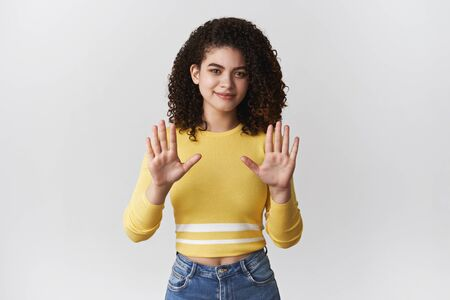 No think pass. Attractive uninterested stylish curly-haired girl rejecting offer raise hands stop refusal gesture smirking apologizing not comming party unwilling participate, white background Stock Photo