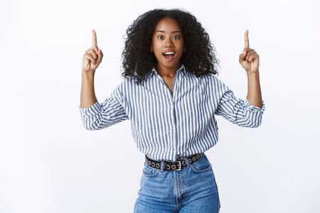 Impressed excited attractive female dark-skinned friend telling you awesome news showing cool promo pointing up index fingers open mouth thrilled amazed standing astonished white background