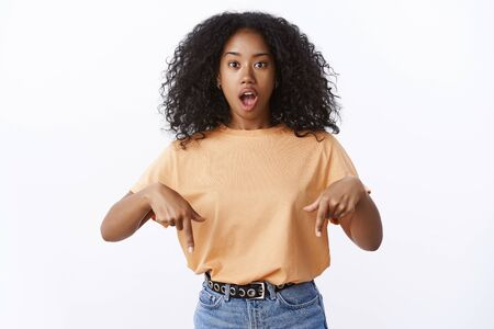 Awesome promo right here. Portrait excited amazed overwhelmed attractive african american woman curly hairstyle open mouth telling you astonishing news pointing index fingers down bottom