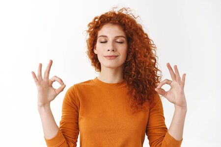 Redhead girl calm down, soothing stress with yoga. Relieved happy ginger woman peacefully meditating, making zen mudra sign, breathing patient, smiling tenderly, inhale positive vibes