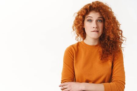 Hesitant and thoughtful gorgeous young redhead woman biting lip squinting look blue eyes camera, thinking how act, making-up plan solve troublesome situation, standing white background