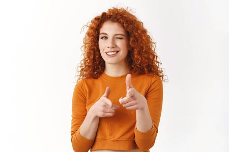 Cheerful redhead woman boost-up confident, encourage friend did great job, pointing finger guns at camera, wink and smile with approval and joy, cheeky grinning congratulate champion with award