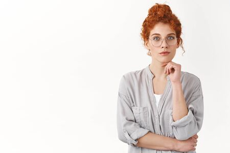 Creative redhead curly woman comb hair in messy-bun, wear glasses look focused and curious, listen carefully interesting idea, contemplate interesting painting, touch chin, gaze camera thoughtful Stock Photo