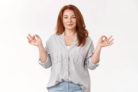 Professional confident mom feel relaxed self-assured unworried. Happy carefree redhead middle-aged woman stay patient smiling peaceful show zen om gesture meditating release stress practice yoga