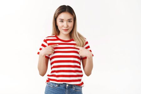 Surprised pleased silly cute asian blond girl pointing herself index fingers pressed chest look camera awaiting result amazed glance asking question is it for me, was chosen picked white background Фото со стока