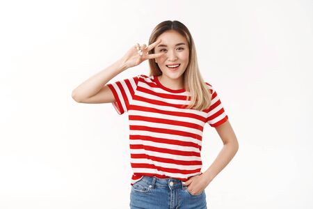 Summer peace vibes. Cheerful active lively charming blond asian girl having perfect energized day show victory gesture eye disco sign smiling broadly toothy positive grin standing white background
