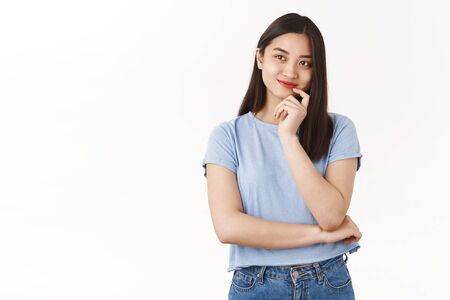 Dreamy creative cheerful young asian girl dark hair smiling delighted touch lip look thoughtful up imaging tasty food pondering thinking curious idea standing creating plan white background