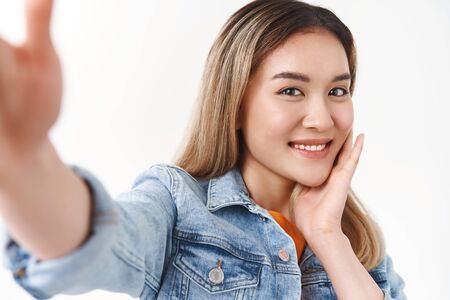 Close-up flirty lovely tender asian blond girl extend arm hold smartphone taking selfie look sweet silly touch cheek softly rub face gentle gaze camera tilt head romantic happy white background Фото со стока