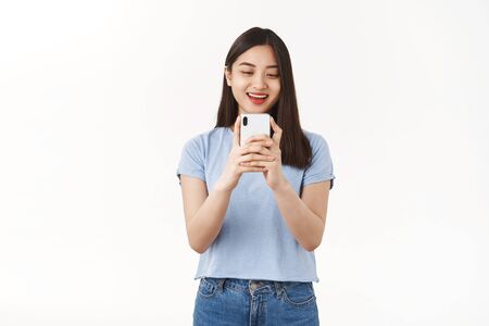 Excited carefree amused asian girl taking picture photographing girlfriend using smartphone camera hold phone look gadget screen amused smiling delighted social media blogger capture moment